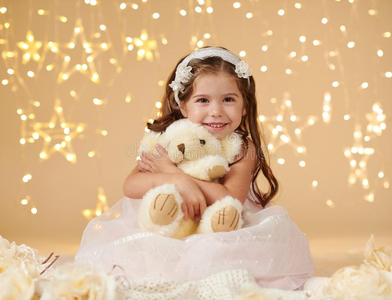 Girl child with bear toy is posing in christmas lights, yellow background, pink dress royalty free stock photography