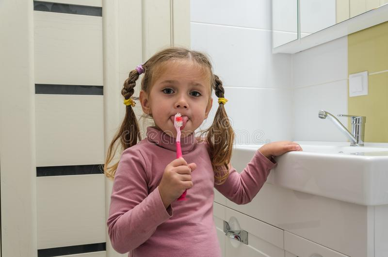 Girl child brushing her teeth with a toothbrush in the bathroom royalty free stock photography