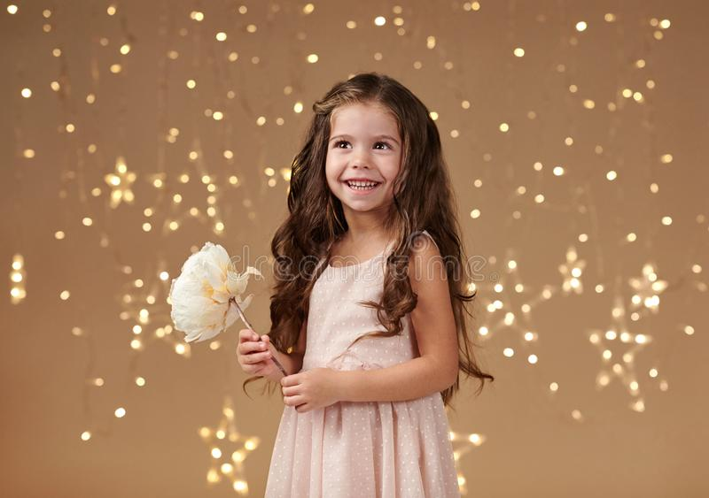 Girl child is in christmas lights, yellow background, pink dress stock photos