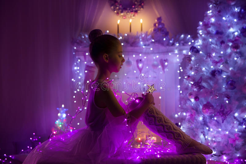 Girl Child, Christmas Tree Lights, Kid in Holiday Night. Girl Child as Angel with Fairy Star, Christmas Tree Lights, Cute Kid in Holiday Night interior room stock photo