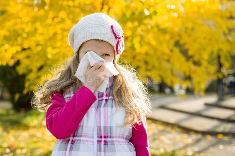 Girl child with cold rhinitis on autumn background, flu season, allergy runny nose.  royalty free stock image