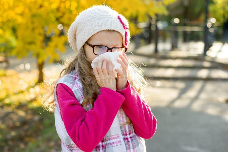 Girl child with cold rhinitis on autumn background, flu season, allergy runny nose.  stock photo