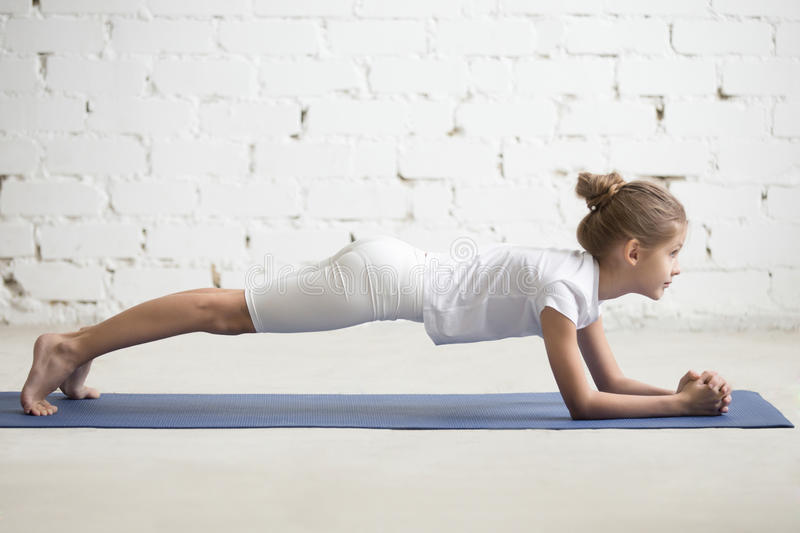 Girl child in Dolphin Plank pose, white studio background. Serious girl child practicing yoga, standing in Dolphin Plank exercise, phalankasana pose working out stock photo