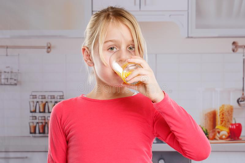Girl child drinking orange juice healthy eating. Kitchen royalty free stock photo