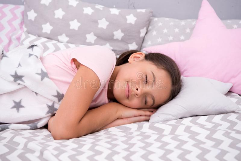 Girl child fall asleep on pillow. Quality of sleep depends on many factors. Choose proper pillow to sleep well. Girl lay. On pillow bedclothes background. Child royalty free stock photo