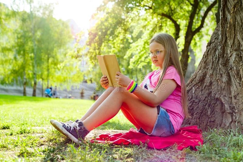 Girl child in glasses reading book in the park royalty free stock image