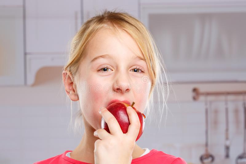 Girl child kid eating apple fruit autumn fall healthy. Kitchen royalty free stock photography