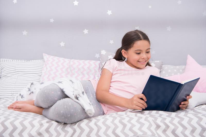Girl child lay bed read book. Kid prepare to go to bed. Pleasant time in cozy bedroom. Girl kid long hair cute pajamas. Relax and read book. Satisfied with royalty free stock images