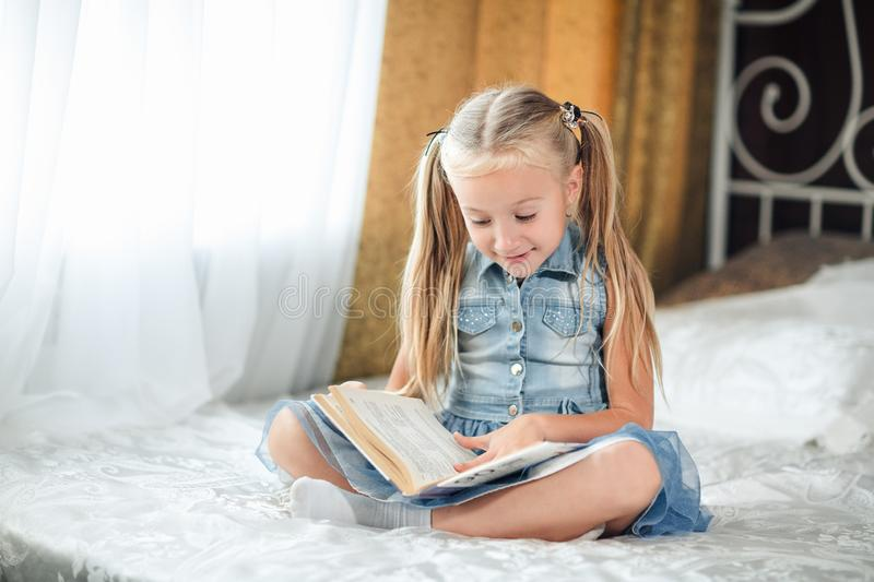 Girl child in denim sundress lay bed read book. Kid prepare to go to bed. Pleasant time in cozy bedroom. Girl kid long hair, relax royalty free stock photo