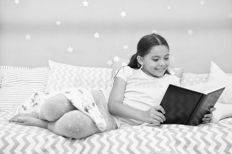 Girl child lay bed read book. Kid prepare to go to bed. Pleasant time in cozy bedroom. Girl kid long hair cute pajamas. Relax and read book. Satisfied with royalty free stock photo