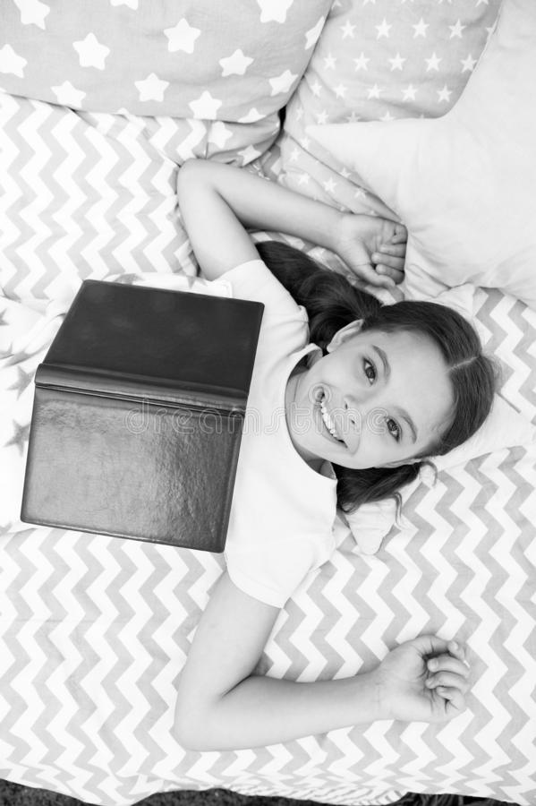 Girl child lay bed read book top view. Kid prepare to go to bed. Pleasant time in cozy bedroom. Girl kid long hair cute. Pajamas relax and read book. Encourage stock photo