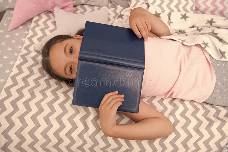 Girl child lay bed read book top view. Kid prepare to go to bed. Pleasant time in cozy bedroom. Girl kid relax and read. Book. Finished reading and satisfied stock photography