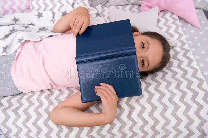 Girl child lay bed read book top view. Kid prepare to go to bed. Pleasant time in cozy bedroom. Girl kid relax and read. Book. Finished reading and satisfied stock photos