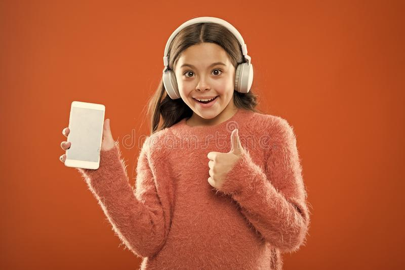 Girl child listen music modern headphones and smartphone. Get music family subscription. Access to millions of songs royalty free stock photo