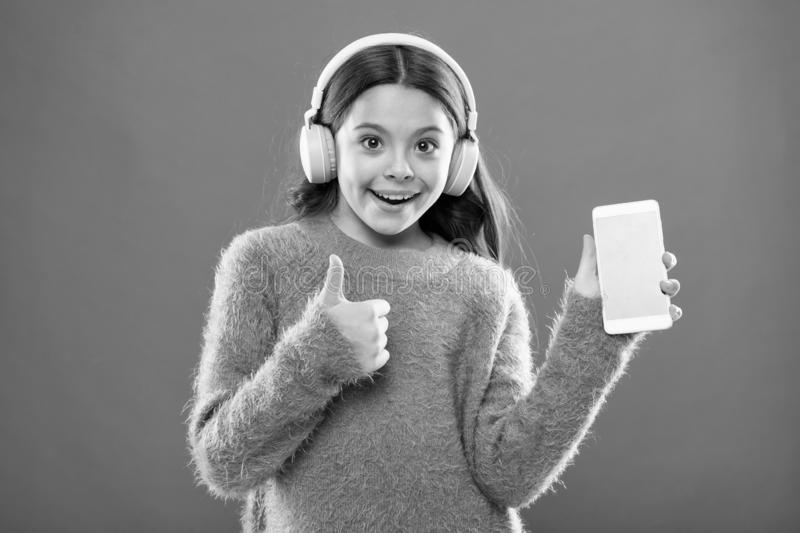 Girl child listen music modern headphones and smartphone. Get music family subscription. Access to millions of songs royalty free stock image