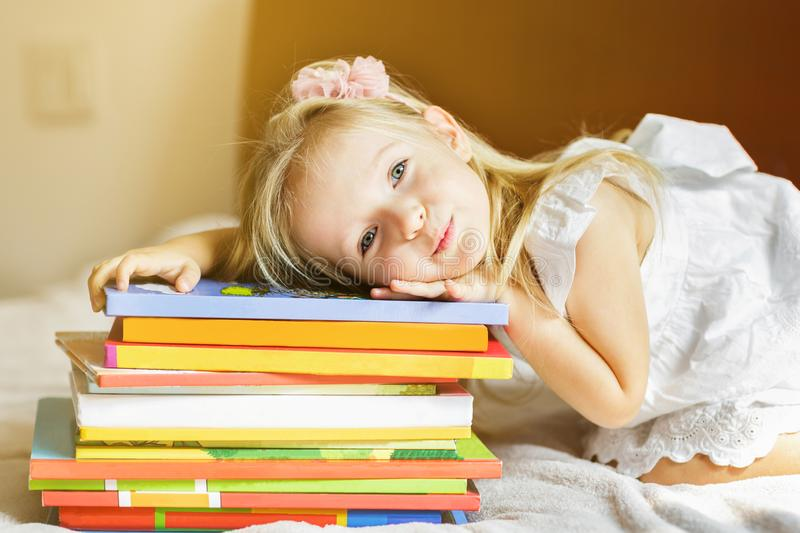Girl child lying on the bed with books. Kid prepare to go to bed. Pleasant time in cozy bedroom. Girl kid relax and read book. Finished reading and satisfied royalty free stock photos