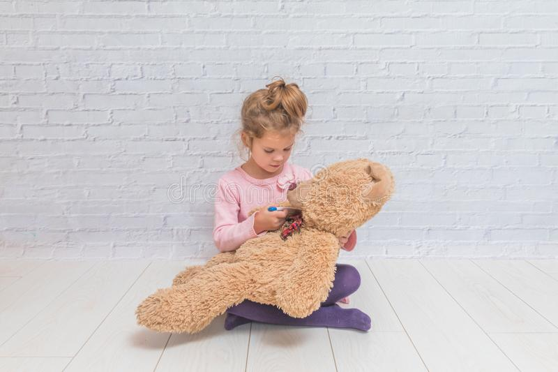 girl, child measures the temperature of a toy bear, against a white brick wall royalty free stock images