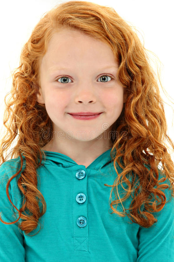 Girl Child with Orange Curly Hair and Blue Eyes. Close Up Girl Child with Orange Curly Hair and Blue Eyes smiling over white background stock photo