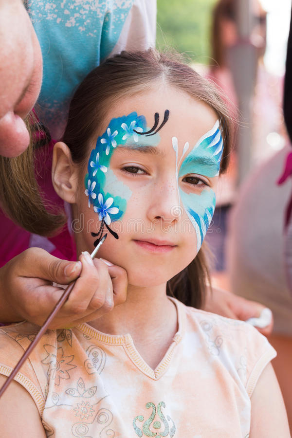 Girl child outdoors in tree with butterfly face painting stock images