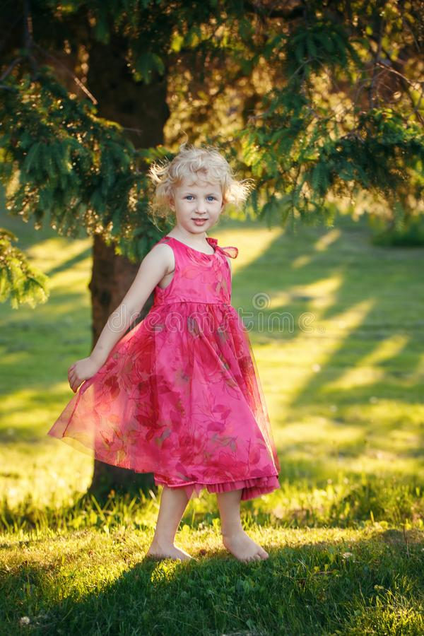 girl child in pink dress standing in field meadow outside. royalty free stock photo