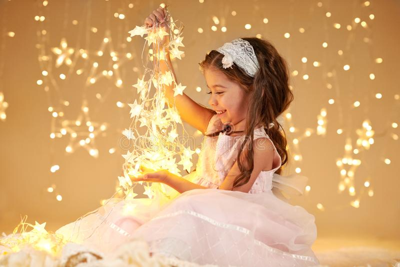Girl child is playing with christmas lights, yellow background, pink dress stock photo