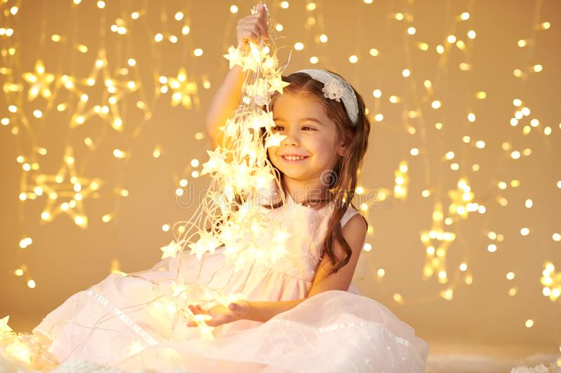 Girl child is playing with christmas lights, yellow background, pink dress stock photos
