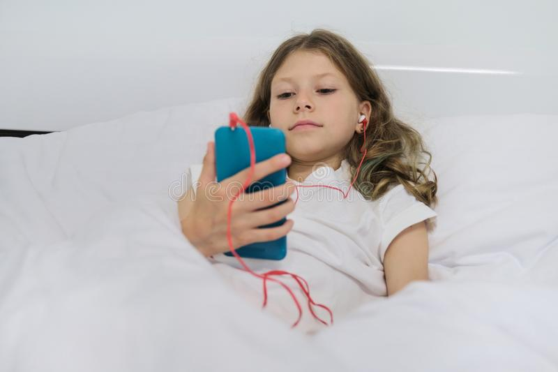 Girl child with mobile phone in headphones, sitting in home white bed royalty free stock photography
