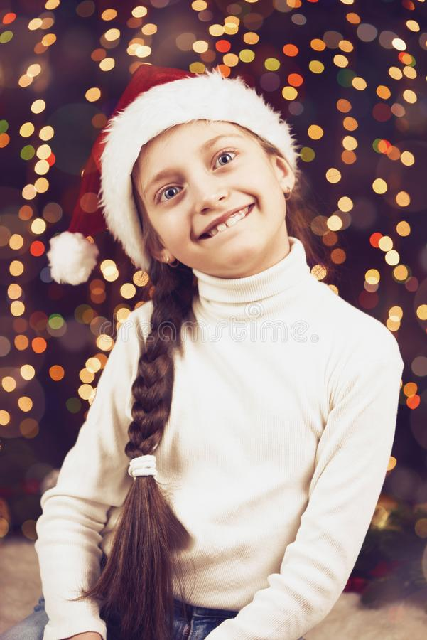 Girl child posing with christmas decoration on dark background, illuminated lights and bokeh, face closeup, dressed in santa hat, royalty free stock photography