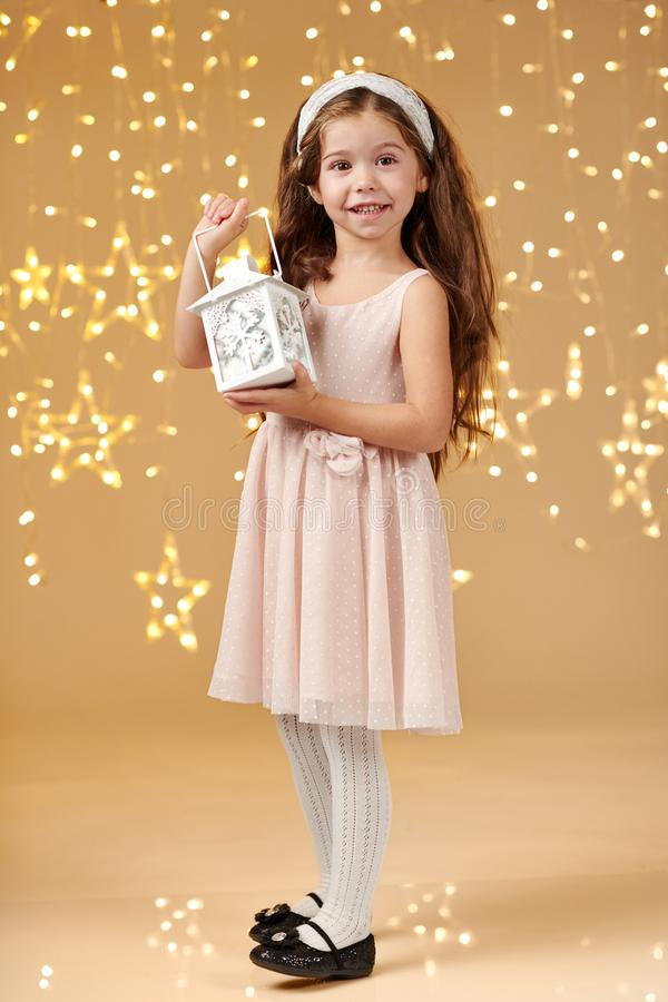 Girl child is posing with lantern in christmas lights, yellow background, pink dress royalty free stock images