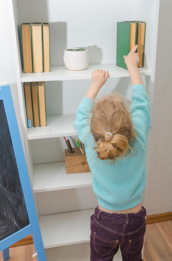 The child puts the book on the shelf stock photo