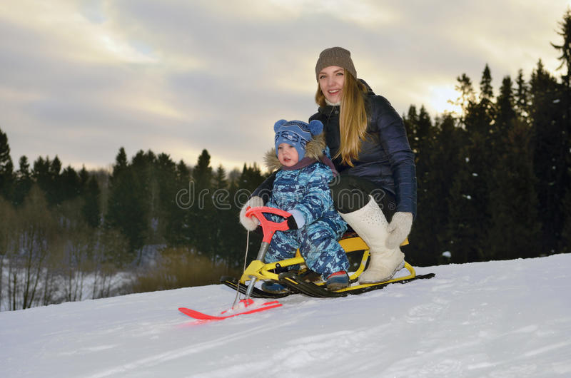 A girl with a child riding on a sledge stock photography