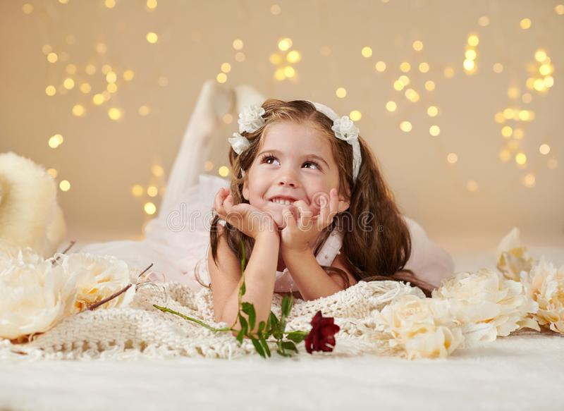 Girl child with rose flower is posing in christmas lights, yellow background, pink dress royalty free stock photos