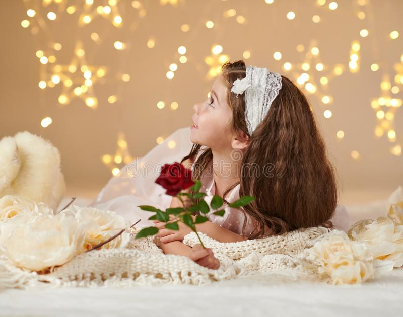 Girl child with rose flower is posing in christmas lights, yellow background, pink dress royalty free stock image