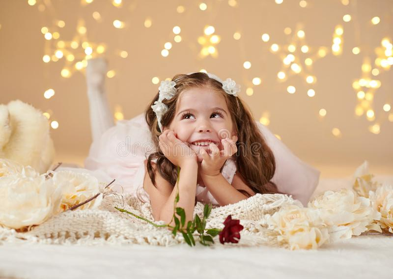 Girl child with rose flower is posing in christmas lights, yellow background, pink dress stock photo