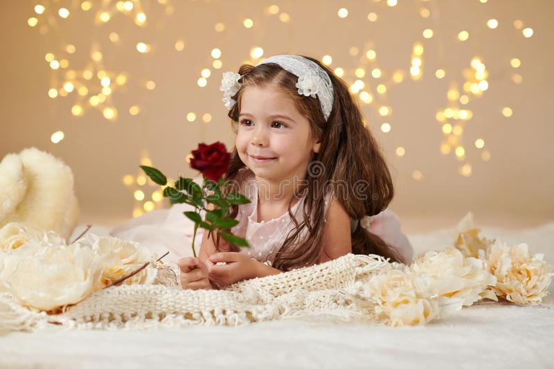 Girl child with rose flower is posing in christmas lights, yellow background, pink dress royalty free stock images