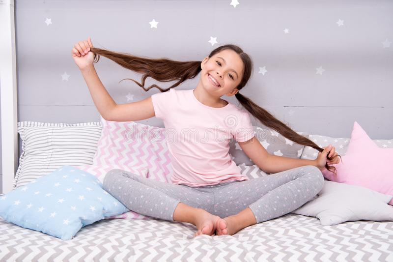 Girl child sit on bed in her bedroom. Kid prepare hair before go to bed. Girl kid long hair cute pajamas relaxing in. Bedroom. Time to sleep or nap. Long hair stock photos