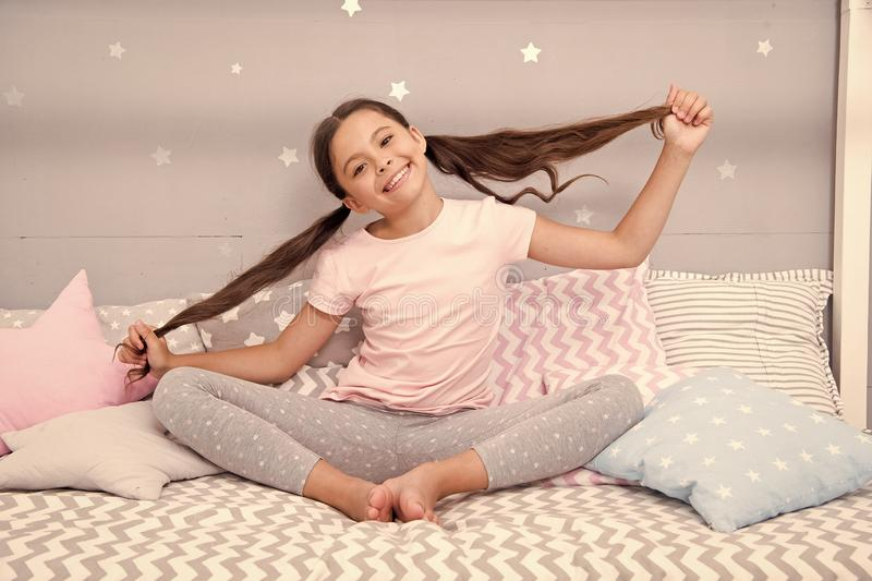 Girl child sit on bed in her bedroom. Kid prepare hair before go to bed. Girl kid long hair cute pajamas relaxing in. Bedroom. Time to sleep or nap. Long hair stock photography