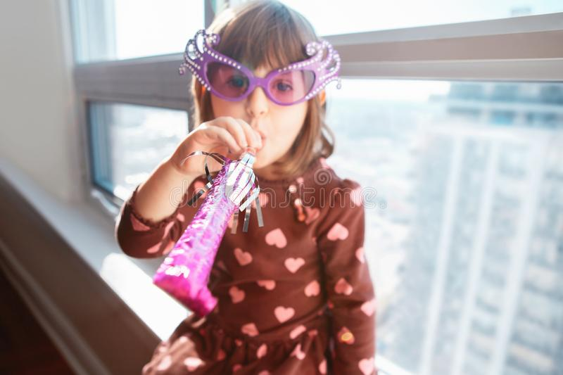 Girl child sitting on window sill at home and blowing whistle trumpet celebrating birthday royalty free stock photography