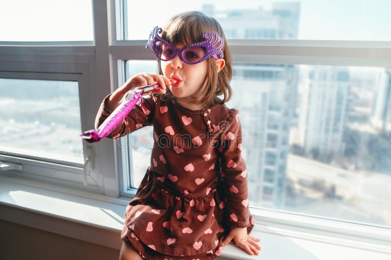 Girl child sitting on window sill at home and blowing whistle trumpet celebrating birthday royalty free stock images
