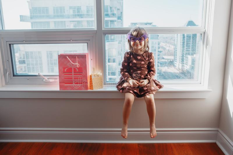 Girl child sitting on window sill at home opening birthday gifts stock photos