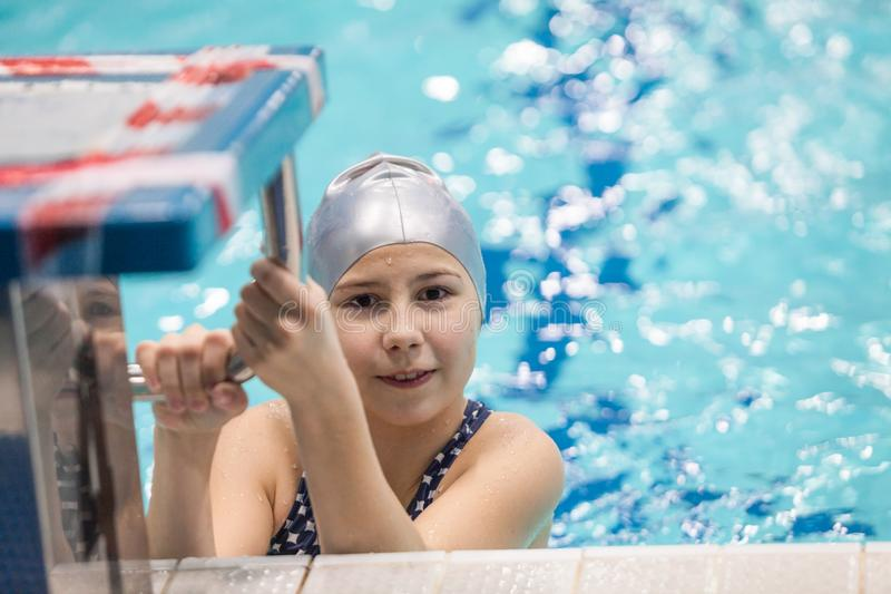 Girl child swimmer in a grey cap hanging on rails of starting stand of swimming pool royalty free stock photos