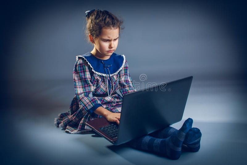 Girl Child Teen 7 years, of European appearance. Brunette is looking into the computer frown on a gray background cross process stock photos
