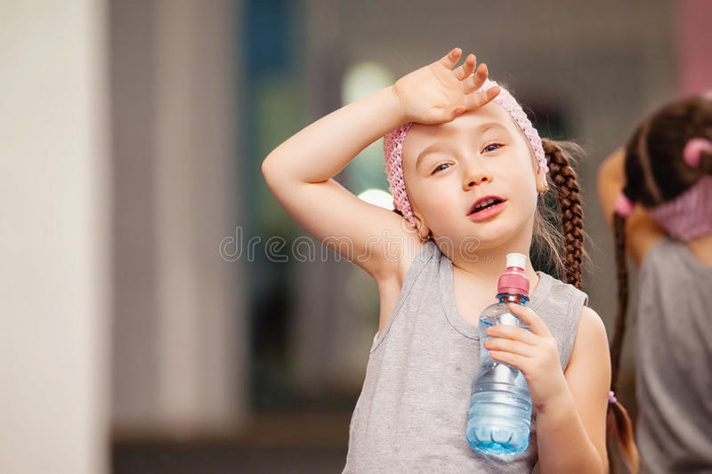 Girl child is tired after training fitness exercises in health club, drink water. royalty free stock images