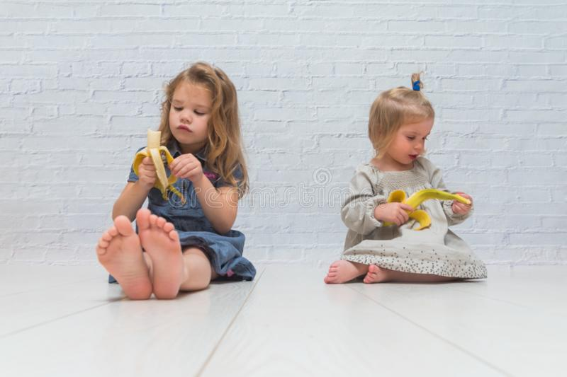 A girl, a child to eat delicious healthy banana against a brick stock photos
