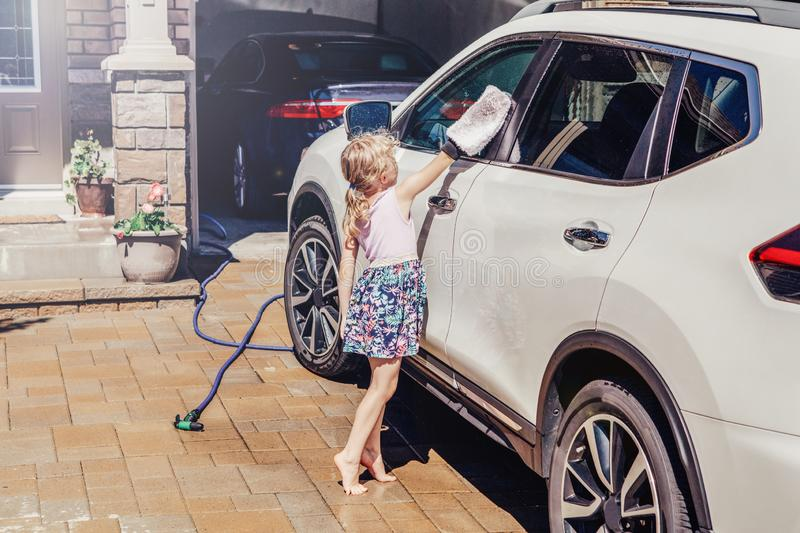 Girl child washing cleaning car. Cute preschool little Caucasian girl child washing cleaning car and wiping glass window on driveway in front house on sunny stock photo