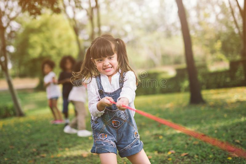 Girl children playing tug of war at the park. stock photo