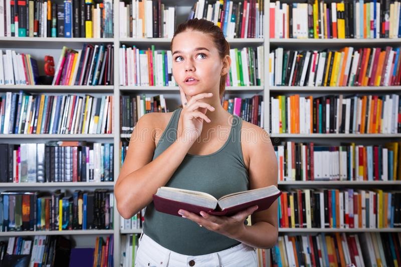 Girl choice of books in the library. Puzzled girl choice of books in the library royalty free stock image