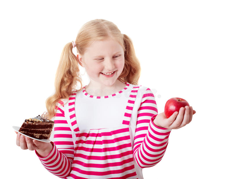 Girl choose from sweet cake and red apple royalty free stock photography