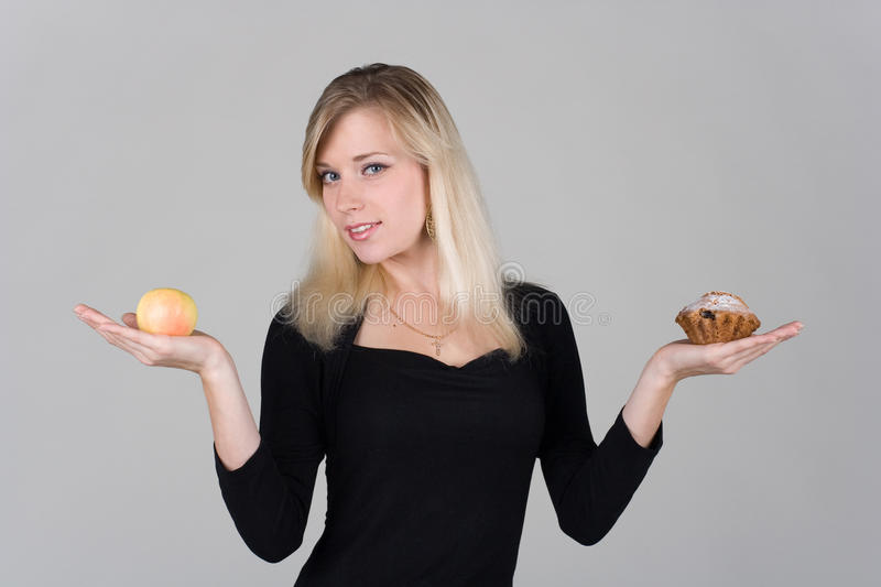 A girl chooses between an apple and a cake royalty free stock image