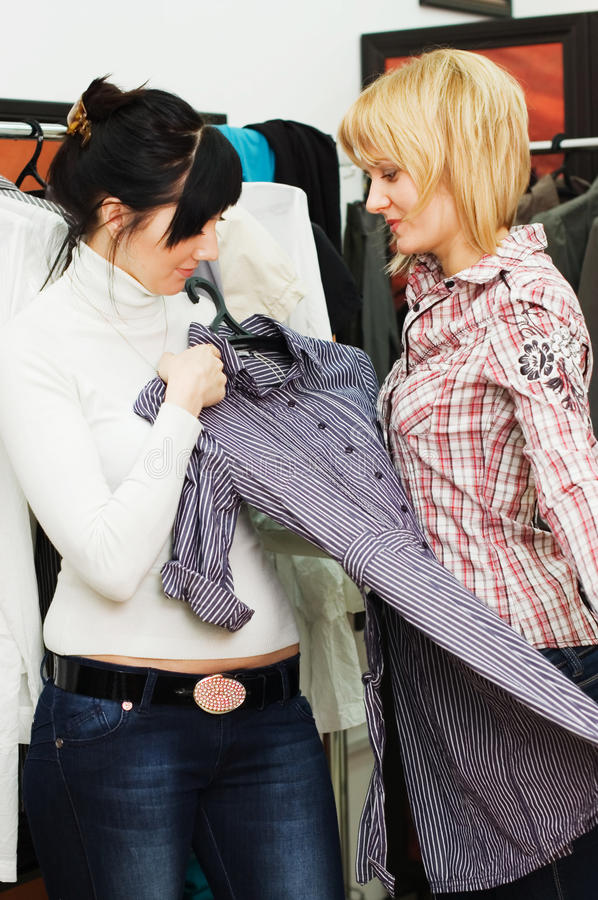 Girl chooses clothes in a boutique royalty free stock images